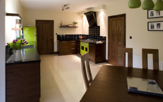 Интерьер классической темной кухни с яркими зелеными акцентами